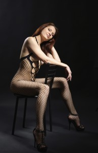 A young woman is straddling on the chair. She is wearing a fishnet bodysuit and high heels.