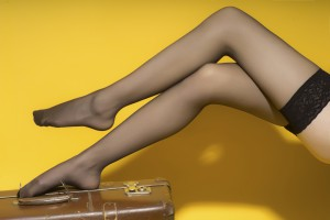 Beautiful slender female legs in black stockings on old brown suitcase on yellow studio background, horizontal picture